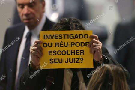 "An opposition lawmakers shows a sign written in Portuguese that reads ""Suspect or defendant can you choose your judge?"" before the beginning of session of the Commission of Constitution and Justice of the Senate, in Brasilia, Brazil, . Brazil's Senate has begun a process that is likely to confirm Brazil's former Minister of Justice Alexandre de Moraes for the country's highest court"