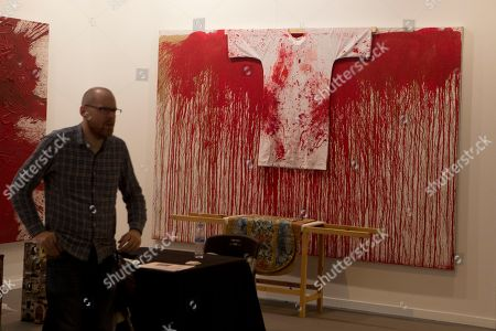 A man stands by an art work by Hermann Nitsch at the Marc Straus - New York gallery at the ARCO International Art Fair in Madrid, Spain, . ARCO runs from Feb. 22 to Feb. 26