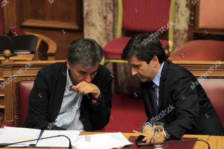 Greek Finance Euclid Tsakalotos (l) Talks with Deputy Finance Minister George Chouliarakis (r) During the Debate in the Greek Parliament On the Omnibus Bill On Prior Actions Which the Government Agreed Upon Between Greece and Its Lenders in Athens Greece 15 October 2015 the Debate Will Be Completed On 16 October with a Voting in the Parliament Plenum