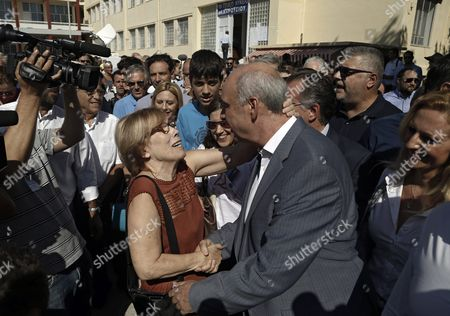 A Supporter Greets the Leader of Main Opposition Consernative 'New Democracy' Party Evangelos Meimarakis (central R) As He Leaves an Election Center in Athens Greece 20 September 2015 Greek Voters Take to the Polls Throughout Greece in General Elections After Prime Minister Tsipras Resigned On 20 August 2015