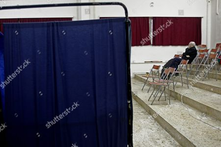 A New Democracy Party Supporter Sits Next to Voting Booths During the Leadership Elections in Athens Greece 10 January 2016 New Democracy Supporters Were Voting in the Final Round of the Partys Leadership Election On Sunday Vangelis Meimarakis Faces Off Against Kyriakos Mitsotakis For New Democracys Presidency