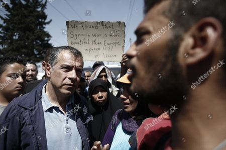 Stock Image of A Syrian Refugee Holds a Placard Reading 'We Found That Syria in War is More Beautiful Than Europe in Peace' While Stavros Theodorakis (l) Leader of 'To Potami' Party Listens to Refugees in the Refugee Camp of Idomeni Near the Greek-fyrom Borders 18 April 2016 a Seriously Injured Refugee Was Rushed to a Hospital From the Camp at Idomeni On the Border Between Greece and the Former Yugoslav Republic of Macedonia the Incident Sparked Tension in the Camp where Residents Attacked a Police Van That They Considered Was Somehow Involved Throwing Stones and Causing Damage to the Vehicle
