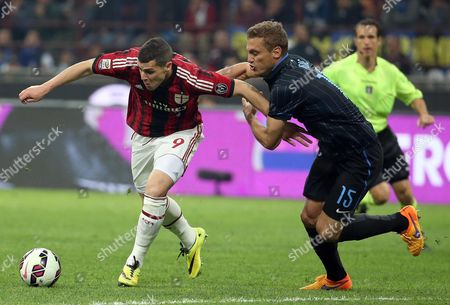 Ac Milan's Mattia Destro (l) in Action Against Inter's Nemanja Vidic During the Serie a Soccer Match Between Inter Milan and Ac Milan at the Giuseppe Meazza Stadium in Milan Italy 19 April 2015