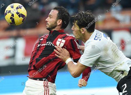 Stock Photo of Milan's Forward Gianpaolo Pazzini (l) and Atalanta's Defender Guglielmo Stendardo (r) in Action During the Serie a Soccer Match Between Ac Milan - Atalanta Bc at the Giuseppe Meazza Stadium in Milan Italy 18 January 2015