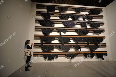 A Woman Stands Next to the Artwork by Greek Artist Jannis Kounellis Displayed in the Italy Pavillion at the 56th International Art Exhibition in Venice Italy 07 May 2015 the Venice Biennale Entitled 'All the World's Futures' Runs 09 May to 22 November