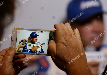 A reporter records an interview with Michael Waltrip during NASCAR Daytona 500 media day at Daytona International Speedway, in Daytona Beach, Fla