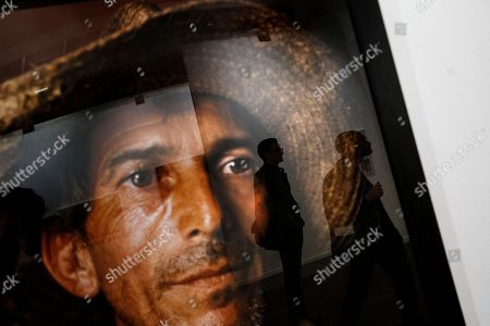 Visitors are reflected in a framed picture by Andres Serrano at the ARCO International Art Fair in Madrid, Spain, . ARCO runs from Feb. 22 to Feb. 26
