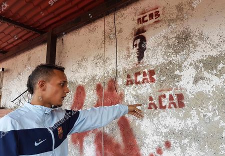 Jhorman Valero points to the image of his late cousin Bassil da Costa, which he stenciled on the terrace wall of his home in Guatire, Venezuela. Valero took his 24-year-old cousin, Bassil da Costa, to join a nationwide protest against the administration of President Nicolas Maduro three years ago. Hours later, Bassil was bleeding in his arms, the first of a rash of young people to be killed by security forces