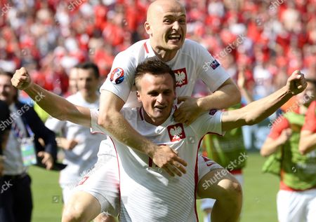Michal Pazdan (up) and Slawomir Peszko of Poland Celebrate After the Uefa Euro 2016 Round of 16 Match Between Switzerland and Poland at Stade Geoffroy Guichard in Saint-etienne France 25 June 2016 (restrictions Apply: For Editorial News Reporting Purposes Only not Used For Commercial Or Marketing Purposes Without Prior Written Approval of Uefa Images Must Appear As Still Images and Must not Emulate Match Action Video Footage Photographs Published in Online Publications (whether Via the Internet Or Otherwise) Shall Have an Interval of at Least 20 Seconds Between the Posting ) France Saint-etienne