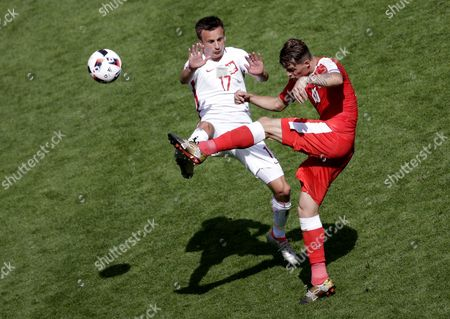 Slawomir Peszko of Poland (l) and Granit Xhaka of Switzerland During the Uefa Euro 2016 Round of 16 Match Between Switzerland and Poland at Stade Geoffroy Guichard in Saint-etienne France 25 June 2016 (restrictions Apply: For Editorial News Reporting Purposes Only not Used For Commercial Or Marketing Purposes Without Prior Written Approval of Uefa Images Must Appear As Still Images and Must not Emulate Match Action Video Footage Photographs Published in Online Publications (whether Via the Internet Or Otherwise) Shall Have an Interval of at Least 20 Seconds Between the Posting ) France Saint-etienne