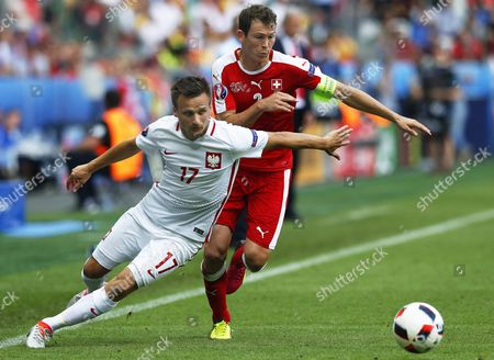 Poland's Slawomir Peszko (l) in Action Against Stephan Lichtsteiner (r) of Switzerland During the Uefa Euro 2016 Round of 16 Match Between Switzerland and Poland at Stade Geoffroy Guichard in Saint-etienne France 25 June 2016 (restrictions Apply: For Editorial News Reporting Purposes Only not Used For Commercial Or Marketing Purposes Without Prior Written Approval of Uefa Images Must Appear As Still Images and Must not Emulate Match Action Video Footage Photographs Published in Online Publications (whether Via the Internet Or Otherwise) Shall Have an Interval of at Least 20 Seconds Between the Posting ) France Saint-etienne