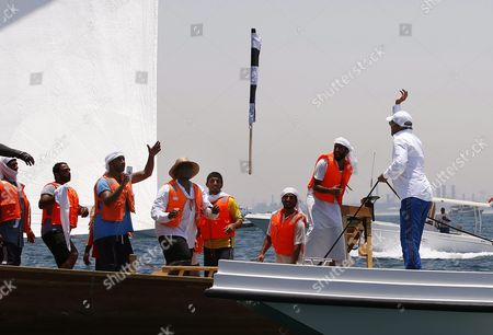 Saeed Hareb (r) Chairman of the Uae Marine Sports Federation Throw's the Winner's Flag to Crew Members of the 'Zilzal' Dhow Boat Owned by H H Sheikh Hamdan Bin Mohammed Bin Rashid Al Maktoum Crown Prince of Dubai and Chairman of Dubai Executive Council Winning the Al Gaffal Dhow Race in Dubai United Arab Emirates 20 May 2016 the Al Gaffal Traditional 60ft Dhow Race is the Biggest Traditional Sailing Race in the World and Sees Traditional Dhow Sailing Vessels Taking Part the Race Begins From Sur Bu Na'air Island Off the Coast of the Uae Heads East Towards the First Check Point at Moon Island 23 60 Nautical Miles From the Start Line and Then Changes Course Slightly For the Final 27 30 Nautical Miles to the Finish Line at Mina Seyahi in the Dubai International Marine Club (dimc) United Arab Emirates Dubai