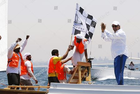 Saeed Hareb (r) Chairman of the Uae Marine Sports Federation Applauds As Crew Members of the 'Zilzal' Dhow Boat Owned by H H Sheikh Hamdan Bin Mohammed Bin Rashid Al Maktoum Crown Prince of Dubai and Chairman of Dubai Executive Council Celebrate After Winning the Al Gaffal Dhow Race in Dubai United Arab Emirates 20 May 2016 the Al Gaffal Traditional 60ft Dhow Race is the Biggest Traditional Sailing Race in the World and Sees Traditional Dhow Sailing Vessels Taking Part the Race Begins From Sur Bu Na'air Island Off the Coast of the Uae Heads East Towards the First Check Point at Moon Island 23 60 Nautical Miles From the Start Line and Then Changes Course Slightly For the Final 27 30 Nautical Miles to the Finish Line at Mina Seyahi in the Dubai International Marine Club (dimc) United Arab Emirates Dubai