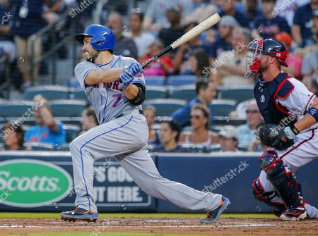 New York Mets Catcher Travis D'arnaud (l) Hits a Two-rbi Single As Atlanta Braves Catcher Tyler Flowers (r) Looks on in the Fourth Inning of the Mlb Baseball Game Between the New York Mets and the Atlanta Braves at Turner Field in Atlanta Georgia Usa 24 June 2016 United States Atlanta