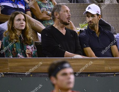 Larry Ellison (c) Executive Chairman of Oracle Corporation and His Girlfriend Ukrainian Actress Nikita Kahn (l) Sit with Serbian Tennis Player Novak Djokovic (r) During the Gael Monfils - Milos Raonic Quarterfinal Match at the Bnp Paribas Open Tennis Tournament in Indian Wells California Usa 17 March 2016 United States Indian Wells