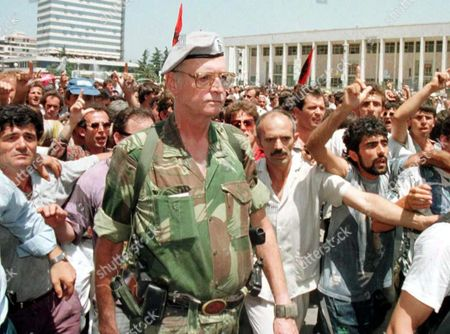 Albanian Would-be King Leka 1 Wears Military Uniforme and Carries Arms As He Heads a Few Hundred Supporters Towards the Building of the Central Electoral Commission Here 03 July Following the Monarchists' Rally in the City's Main Square Bursts of Gunfire Broke out and Several Loud Explosions Echoed Off Buildings and Surrounding Hills One Person was Reportedly Killed in the Shooting Albania Tirana