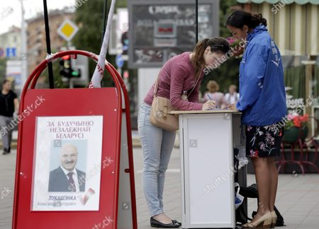 Stock Picture of A Supporter of the Potential Belarussian Presidential Candidate and Current Belarussian President Aleksandr Lukashenko Signs a Petition in Support of Her Candidate in Minsk Belarus 29 July 2015 the Presidential Elections in Belarus Will Be Held on 11 October 2015 Belarus Minsk