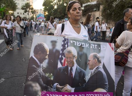 An Israeli Marcher Holds a Sign Showing the Historic Handshake at the White House Between Us President Jimmy Carter (c) Egyptian President Anwar Sadat (l) and Israeli Prime Minister Nenachem Begin (r) As She Takes Part in the March to the Jerusalem Residence of Israeli Prime Minister Benjamin Netanyahu During the Conclusion of the Women Wage Peace March Across Israel 19 October 2016 About 1 000 Women Including Many Israeli Arabs Marched the Slogan 'Yes It is Possible' is on the Photograph Israel Jerusalem