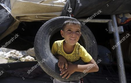 A Palestinian Boy From the Khirbet Susiya Community Plays with a Tyre Next to the Family Tent Near Hebron West Bank 20 July 2015 Palestinian News Agency of Mann Report the Israeli Civil Administration Had Informed the Populations Through Their Lawyers That It Will Demolish Some of the Facilities of the Community After the Muslim Feast of Eid Al-fitr the Israeli Supreme Court Decided on 04 May 2015 to Deport the 450 Inhabitants of Khirbet Susiya Under the Pretext of the Lack of Infrastructure For the Region - Khirbet Susiya