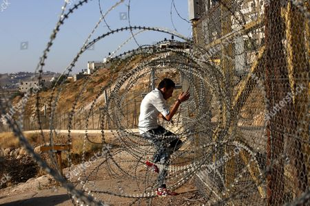 A Young Palestinian Mann Climbs Through a Barb Wire Enforced Barrier Fence Near the West Bank City of Bethlehem in an Attempt to Enter Jerusalem to Attend the Second Friday Prayers in the Muslim Holy Month of Ramadan at the Al-aqsa Mosque in the Muslim Holy Month of Ramadan 17 June 2016 Israeli Authorities the Week Before Only Allowed Access to Jerusalem For Women and Children and Limited the Age of Men to Those Over 45 Muslims Around the World Celebrate the Holy Month of Ramadan by Praying During the Night Time and Abstaining From Eating and Drinking During the Period Between Sunrise and Sunset Ramadan is the Ninth Month in the Islamic Calendar and It is Believed That the Korans First Verse was Revealed During Its Last 10 Nights - Bethlehem