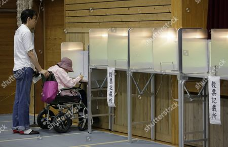 Stock Image of A Woman Voter on a Wheelchair is Assisted by a Staff of Local Electoral Management Committee to Fill Her Ballot For Tokyo Gubernatorial Election at a Polling Station in Tokyo Japan 31 July 2016 the Election is Voted on 31 July to Select the Successor to Yoichi Masuzoe who Resigned Over His Usage of Political Fund About 9 867 000 Voters Select a Governor From 21 Candidates Running For the Gubernatorial Election in the Tokyo Metropolitan with a Population of About 13 617 000 Japan Tokyo