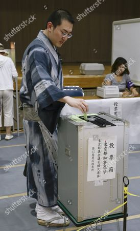 Stock Photo of A Tokyo Voter Casts His Ballot For Tokyo Gubernatorial Election at a Polling Station in Tokyo Japan 31 July 2016 the Election is Voted on 31 July to Select the Successor to Yoichi Masuzoe who Resigned Over His Usage of Political Fund About 9 867 000 Voters Select a Governor From 21 Candidates Running For the Gubernatorial Election in the Tokyo Metropolitan with a Population of About 13 617 000 Japan Tokyo