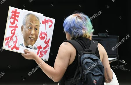 A Man Holding a Placard with Tokyo Governor Yoichi Masuzoe's Portrait and the Words 'Do not Quit Masuzoe!' Walks Past the Tokyo Metropolitan Government Office in Tokyo Japan 15 June 2016 Earlier in the Day Tokyo Governor Yoichi Masuzoe Handed in His Resignation After Receiving Criticism on His Usage of Political Funds Japan Tokyo
