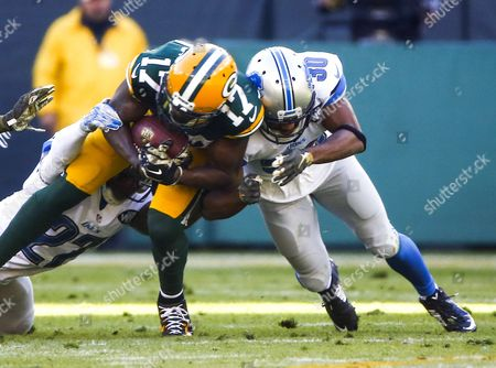Green Bay Packers Wide Receiver Davante Adams (c) is Tackled by Detroit Lions Free Safety Glover Quin (l) and Detroit Lions Defensive Back Josh Wilson (r) After Catching a Pass in the First Half of the Nfl American Football Game Between the Detroit Lions and the Green Bay Packers at Lambeau Field in Green Bay Wisconsin Usa 15 November 2015 United States Green Bay