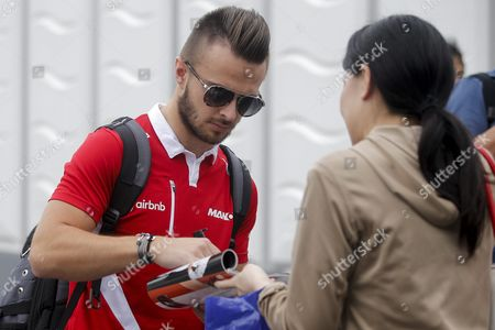 British Formula One Driver Will Stevens (l) of Manor Marussia F1 Team Signs an Autograph For a Japanese Fan Ahead of the Japanese Formula One Grand Prix at the Suzuka Circuit in Suzuka Central Japan 27 September 2015 Japan Japan