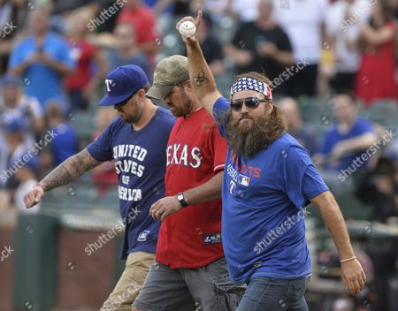 Duck Dynasty Tv Show Star Willie Robertson (r) Walks Onto the Field with Navy Seals Marcus Luttrell (l) and His Brother Morgan Luttrell (c) to Throw out the First Pitch Before the New York Yankees Game Against the Texas Rangers at Globe Life Park in Arlington Texas Usa 27 July 2015 United States Arlington