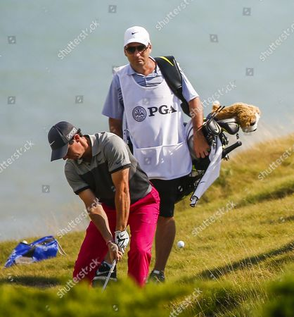 Caddy Jp Fitzgerald (r) Watches As Rory Mcilroy of Northern Ireland Hits His Ball From the Rough Onto the Fairway During Round One of the 97th Pga Championship Golf Tournament at Whistling Straits in Kohler Wisconsin Usa 13 August 2015 United States Kohler