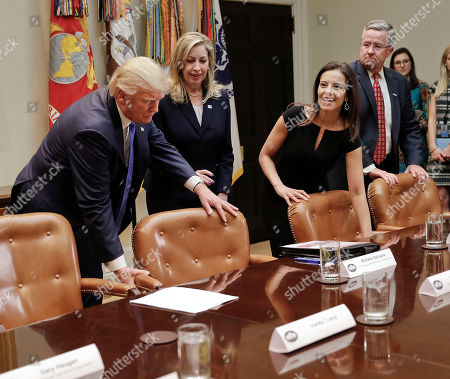 Donald Trump, Michelle Delaune, Dina Powell, Brian Gallagher President Donald Trump pulls a chair out for Michelle DeLaune, from the National Center for Missing and Exploited Children, center before the start of their meeting on domestic and international human trafficking, in the Roosevelt Room of the White House in Washington.Dina Powell, White House Senior Counselor for Economic Initiatives and Brian Gallagher CEO, United Way Worldwide watch
