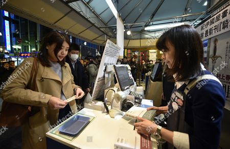 A young woman buys copies of Japanese best-selling author Haruki Murakami new book 'Kishidancho Goroshi' or 'Killing Commendatore' at Kinokuniya bookstore in Shinjuku district, Tokyo, Japan, just after midnight on 24 February 2017. The new book by Murakami is published in two parts. Publisher printed 700,000 copies of the first part and 600,000 of the second.