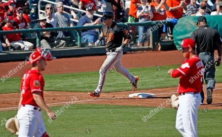 San Francisco Giants second baseman Joe Panik, top, rounds the bases after hitting a two-run home run against Cincinnati Reds starting pitcher Robert Stephenson, right, who get a visit from catcher Stuart Turner, left, during the third inning of a spring training baseball game, in Goodyear, Ariz. The Giants defeated the Reds 9-5