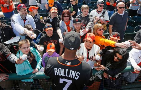 San Francisco Giants shortstop Jimmy Rollins gives autographs to fans prior to a spring training baseball game against the Cincinnati Reds, in Goodyear, Ariz