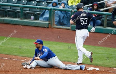 Texas Rangers first baseman James Loney, left, stretches out to make a catch to get Cleveland Indians catcher Adam Moore (53) out at first base during the fourth inning of a spring training baseball game, in Goodyear, Ariz