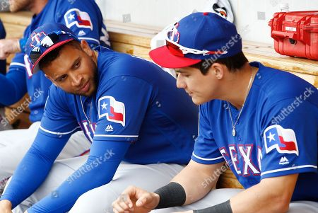 Texas Rangers first baseman James Loney, left, talks with Jose Cardona, right, prior to a spring training baseball game against the Cleveland Indians, in Goodyear, Ariz. The Indians defeated the Rangers 3-2
