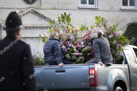 A pickup truck is used to remove floral arrangements