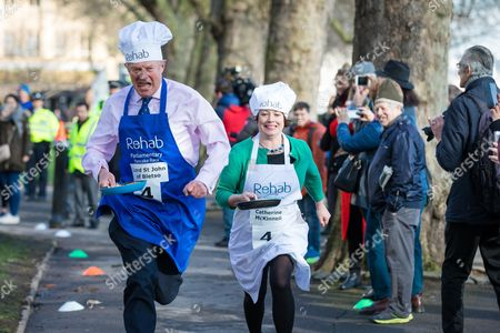 Stock Picture of Lord St John of Bletso overtakes Catherine McKinnell MP on the home straight during the annual Parliamentary Pancake Race.