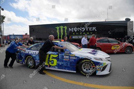 Crew members push Michael Waltrip (15)'s car through the garage area during a practice session for Sunday's NASCAR Daytona 500 auto race at Daytona International Speedway, in Daytona Beach, Fla
