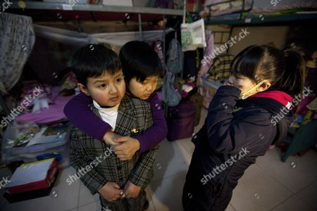 A Picture Made Available on 30 July 2015 Member of 'Longzaitian' Or 'Dragon in the Sky' Shadow Puppet Troupe Wang Wenbin (l) 24 is Hugged by Fellow Member Sun Li (c) 22 During a Moment of Camaraderie While Jia Pan 22 Looks on in Their Dormitory in Beijing China 29 January 2013 China Beijing