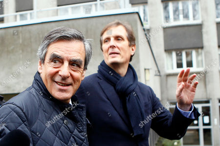 Conservative presidential candidate Francois Fillon, left, leaves his campaign headquarters with his spokesman Jerome Chartier after delivering a speech in Paris, . Fillon is refusing to quit the race despite receiving a summons Wednesday to face charges for alleged fake parliamentary jobs for his family