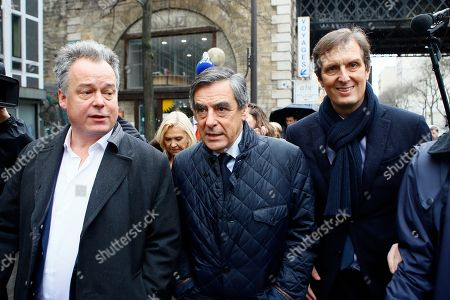 Conservative presidential candidate Francois Fillon, center, leaves his campaign headquarters with his spokesman Jerome Chartier, right, after delivering a speech in Paris, . Fillon is refusing to quit the race despite receiving a summons Wednesday to face charges for alleged fake parliamentary jobs for his family. Man at left is unidentified