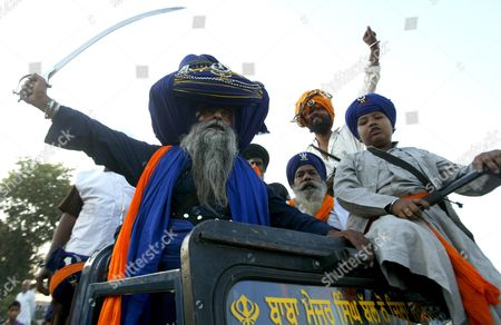 A Man Whose Ancestors Belonged to Sikh Warrior Clan Baba Major Singh (l) Wearing an Oversized Turban Takes out His Sword As He Along with Others Takes Part in a Religious Procession Called 'Mohalla' in the Northern Indian City of Amritsar 27 October 2011 the Procession is Carried out a Day After the Diwali Festival to Mark the 'Bandi Chorh Diwas ' the Day when Guru Hargobind the Sixth 'Guru' Or the Master of the Sikhs Reached Amritsar After His Release From Gwalior Fort During the Reign of Mughal Emperor Jahangir Each Year Members of Various Major Nihang Groups Display Their Martial Arts and Horse Riding Skills During the Mohalla Festival India Amritsar