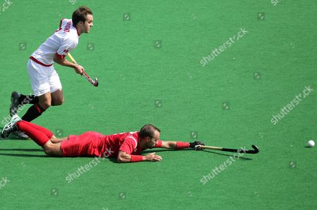 Stock Image of Poland's Miroslaw Kluczka (r) Falls As He Tackled by Canda's Philip Wright (l) During the Men's Field Hockey Olympic Qualification Match Between Canada Vs Poland Held in New Delhi India on 19 February 2012 India New Delhi