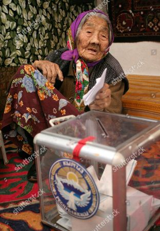 An Elderly Kyrgyz Woman Casts Her Ballot Into a Portable Ballot Box at His House During Early Kyrgyzstan Presidential Voting in the Village of Strelnikovo Some 25 Km From Bishkek Kyrgyzstan 29 October 2011 Kyrgyzstan Will Elect a New President on 30 October in a Vote That Will Also Determine Whether Central Asia's Only Democratic State Can Remain Free of Dictators Around 20 Candidates Are Vying to Take Over From Incumbent President Roza Otunbayeva an Interim Leader Appointed to the Job After the Ouster of President Kurmanbek Bakiyev who was Toppled by Bloody Protests in April 2010 Kyrgyzstan Strelnikovo