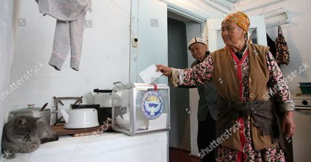 An Elderly Kyrgyz Man Looks at His Wife Casting Her Ballot Into a Portable Ballot Box During Early Kyrgyzstan Presidential Voting at Their House in the Village of Strelnikovo Some 25 Km From Bishkek Kyrgyzstan 29 October 2011 Kyrgyzstan Will Elect a New President on 30 October in a Vote That Will Also Determine Whether Central Asia's Only Democratic State Can Remain Free of Dictators Around 20 Candidates Are Vying to Take Over From Incumbent President Roza Otunbayeva an Interim Leader Appointed to the Job After the Ouster of President Kurmanbek Bakiyev who was Toppled by Bloody Protests in April 2010 Kyrgyzstan Strelnikovo