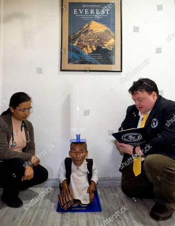 Nepalese Man Chandra Bahadur Dangi (c) is Going Through Final Height Verification Process As Craig Glenday (r) Chief Editor of Guinness World Record Book (r) Looks on at Cwic Hospital in Kathmandu Nepal 26 February 2012 Guinness World Record Team is Due to Hand Over the Certificate to Dangi 72 As a World Shortest Man Later the Same Day Junrey Balawing of the Philippines is Currently Recognized by Guinness World Records As the World's Shortest Man the 72-year-old Dangi Claims to Be Only 22 Inches (56 Centimeters) Tall the Person (l) is an Unidentified Aide Nepal Kathmandu