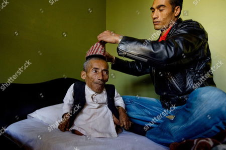 Nepalese Man Chandra Bahadur Dangi (l) is Prepared by His Nephew Son Dolak Dangi Before Leaving For Final Verification and Certification Distribution Ceremony by Guinness World Record Team in Kathmandu Nepal 26 February 2012 Dangi who Lives in Dang District Some 540 Km Southwest of the Capital Came to Kathmandu with the Hope of Being Able to Prove He is the World's Shortest Man the 72-year-old Claims to Be Only 22 Inches (56 Centimeters) Tall a Team of Guinness Judges Led by Craig Glenday a Chief in Editor is in Kathmandu For the Evaluation Junrey Balawing of the Philippines is Currently Recognized by Guinness World Records As the World's Shortest Man Nepal Kathmandu