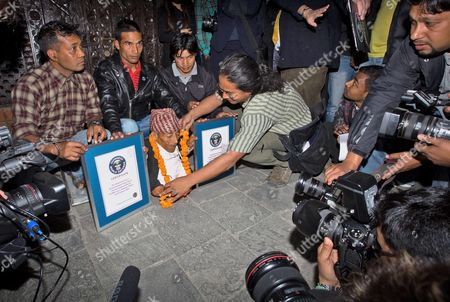 An Unidentified Nepalese Man Garlands Chandra Bahadur Dangi (c) After He was Officially Recognized and Certified the 'Shortest Man Ever' and 'Shortest Man Living' by Guinness World Records During a Ceremony in Kathmandu Nepal 26 February 2012 the Guinness Team Led by Craig Glenday (unseen) Chief Editor of Guinness Book of Records Hand Over the Certificates For the Shortest Man Living who is Measuring 54 6 Centimeters (21 5 Inches) Nepal Kathmandu